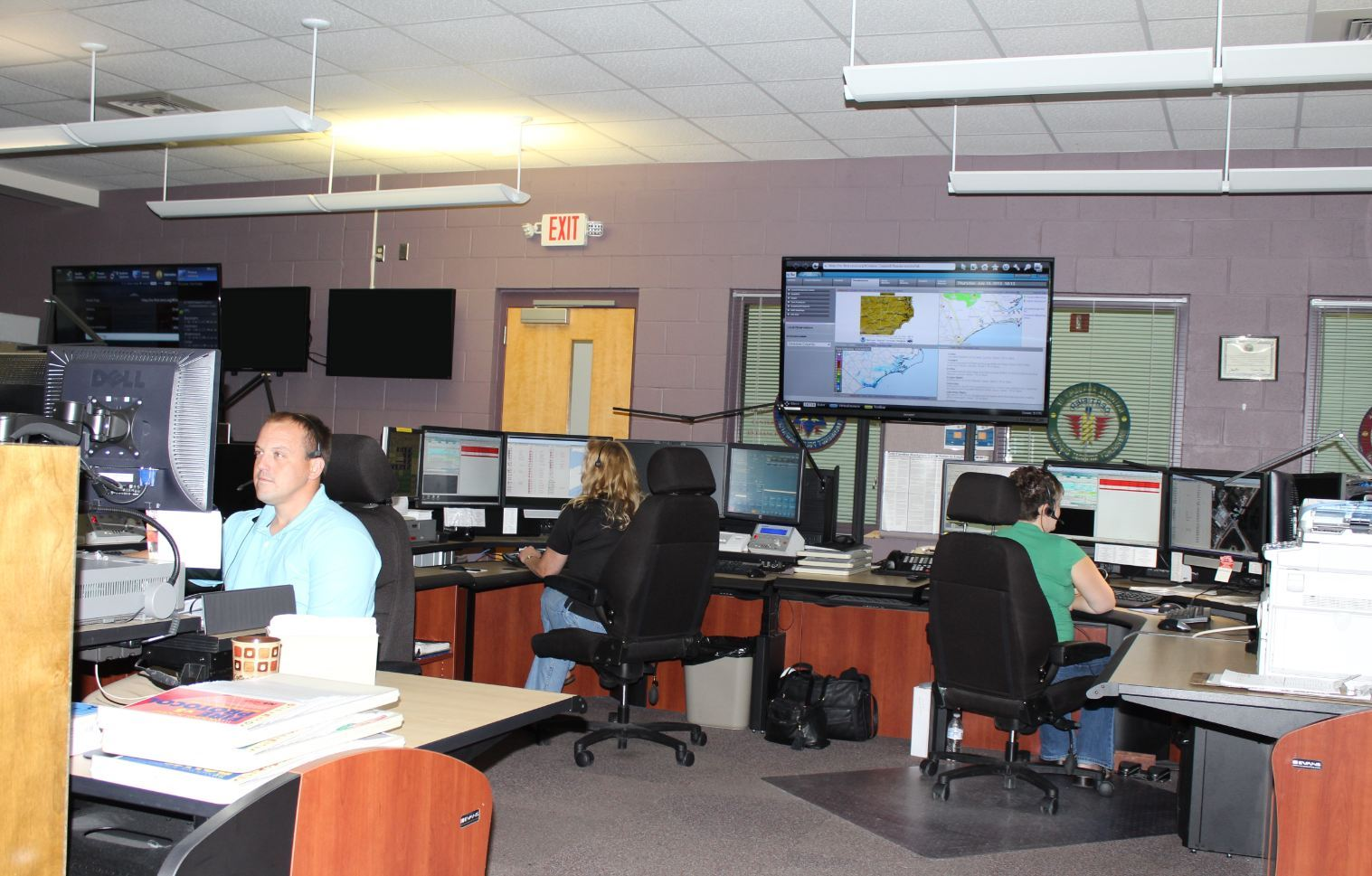 Telecommunicators at their desks prepared to take emergency calls.